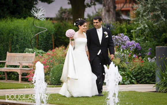 Couple walking in the gardens amongst the fountains at the Grove Hotel