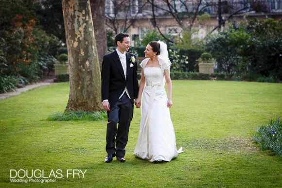 Bride and groom photographed walking in front of Berekeley Hotel in London