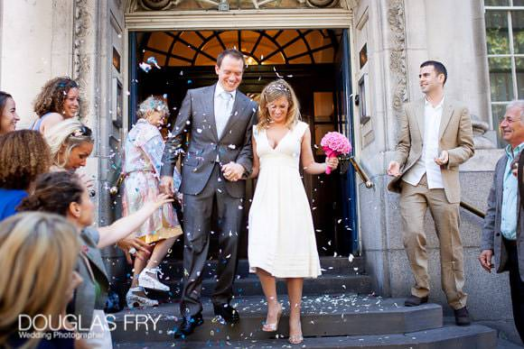 Pink Colour bouquet at Chelsea Register Office - couple on steps with confetti