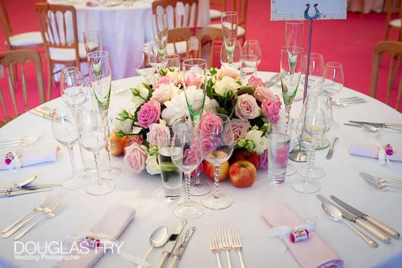 Pink flowers on wedding breakfast tables in marquee