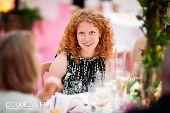 Wedding photography of guests at tables - featuring pink carpet behind