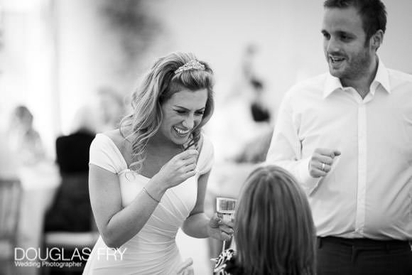Black and white wedding photograph of bride laughing