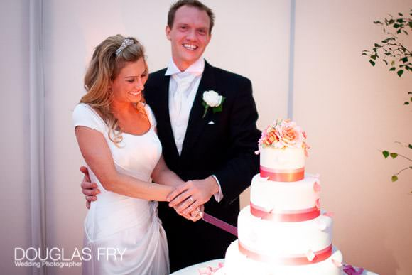 Cutting the cake - wedding cake with pink flowers and tiers