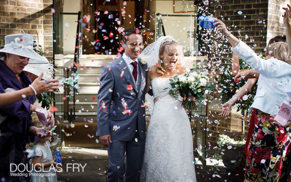 wedding photograph capturing confetti being thrown as couple leave the church steps at HTB