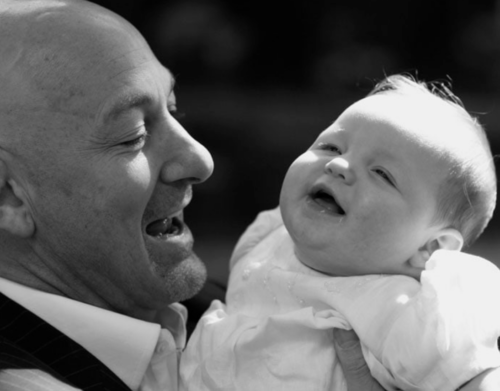 father and baby photographed at London chirstening