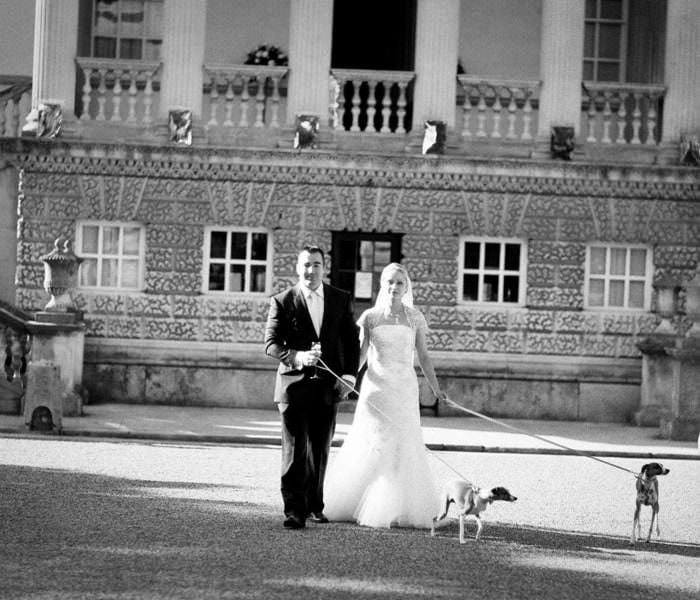 Wedding photograph of bride and groom in front of Chiswick House with their dogs.