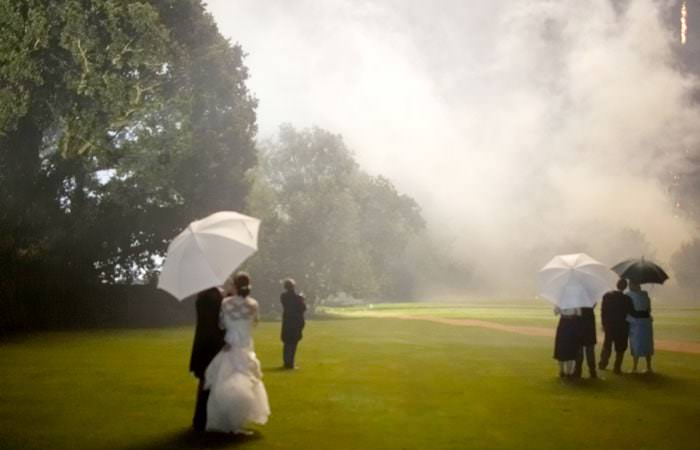 bride and groom watching the fireworks under an umbrella in the rain
