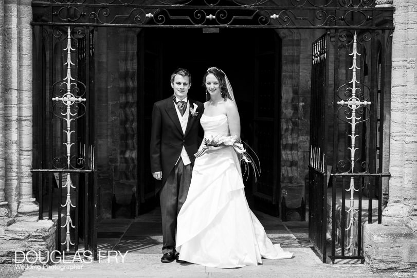 Bride and groom standing in front of Sherborne Abbey in Dorset - black and white photograph