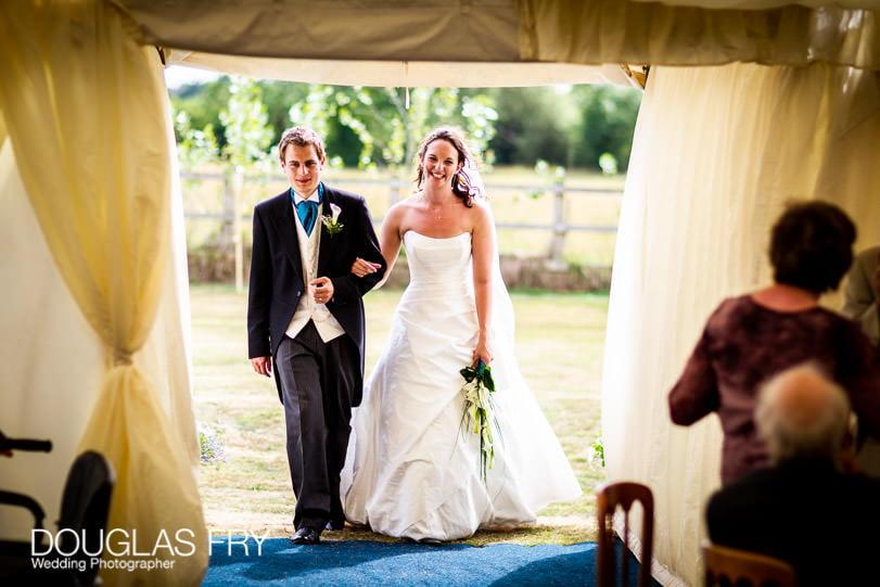 Wedding photographer Dorset - couple entering marquee
