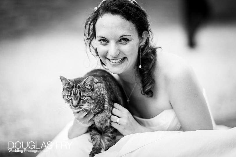 Bride photographed with cat at wedding reception in Dorset