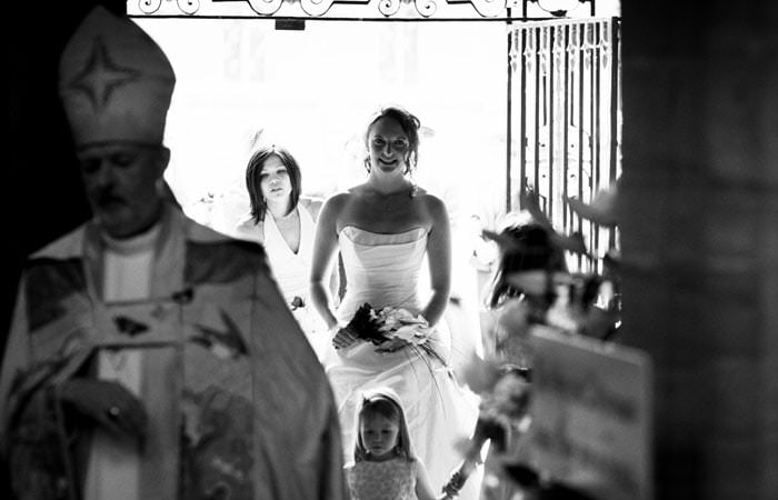 Wedding photograph in black and white of Rosie entering Sherborne Abbey, Dorset