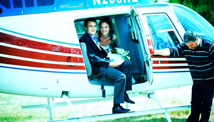 Wedding photograph of Rosie and Mark getting out of helicopter at the reception in Somerset