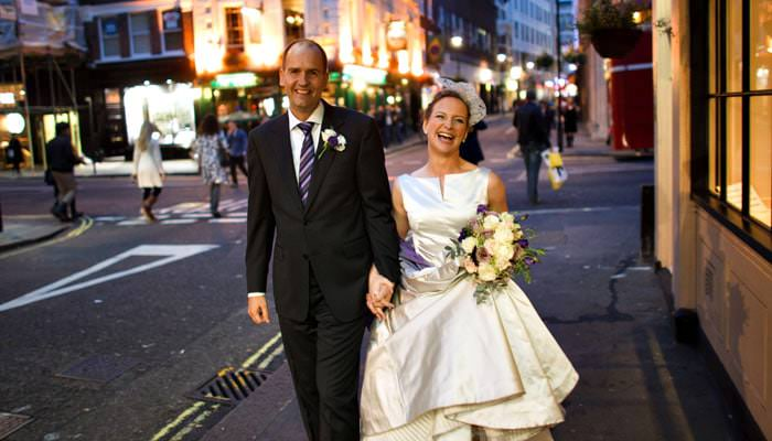 Wedding photograph of bride and groom outside restaurant in Soho, London