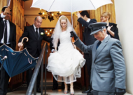 Wedding Photographer london - bride with umbrella leaving synagogue