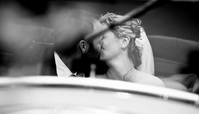 Wedding Photograph Bride and Groom Kissing in Car