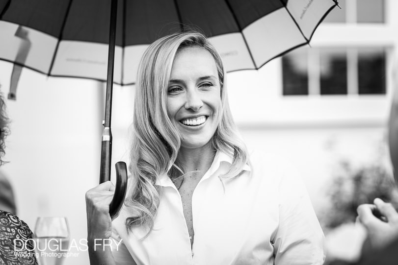 Guest photographed with umbrella at wedding reception