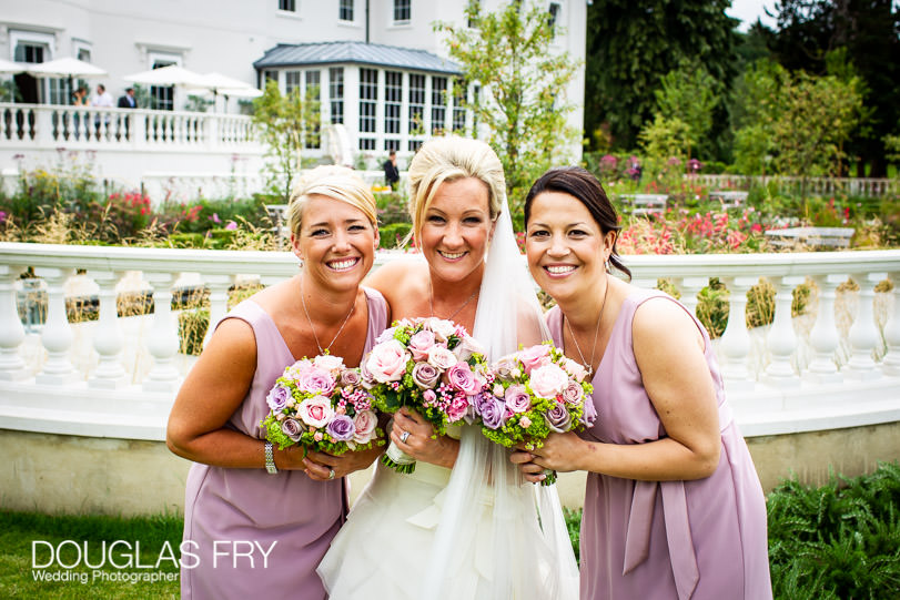 Bride with bridesmaids photographed in front of Coworth Park during wedding reception