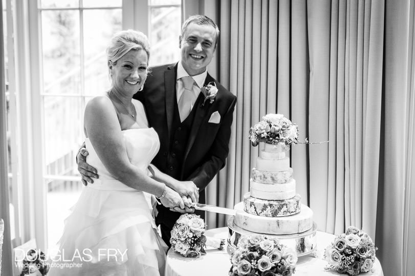 Wedding photograph of couple cutting wedding cake made of cheeses