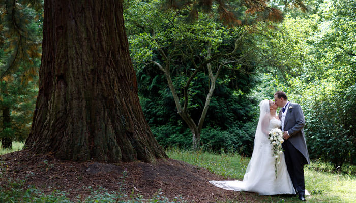 Bride and groom kissing outside under a tree in Cambridgeshire