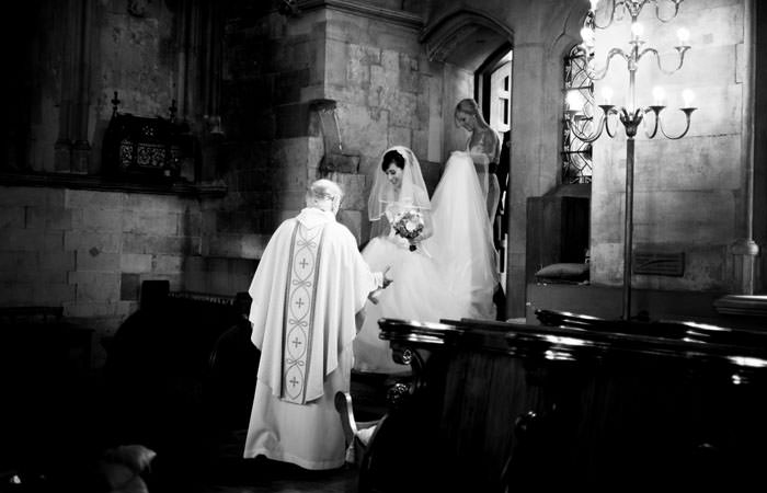 Bride and Vicar Photographed at Wedding at St Etheldredas London