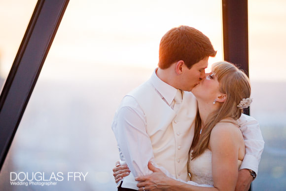 Wedding photograph of couple kissing with sunset behind view out of Gherkin window