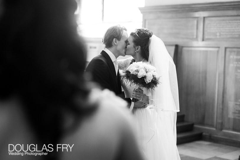Wedding Photographer St Brides Church London - kiss in church