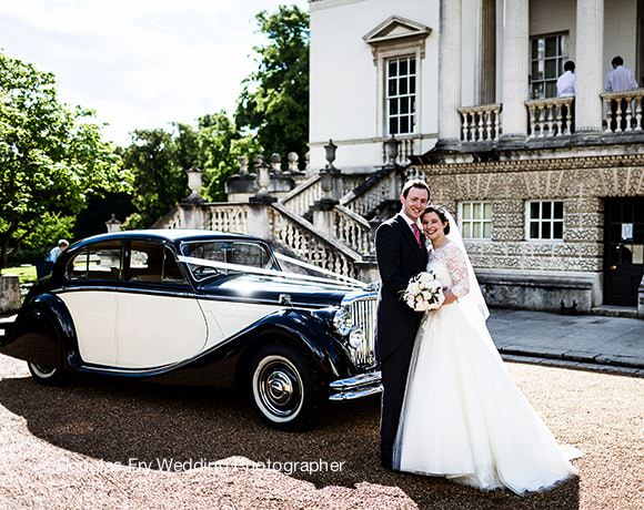 Wedding Photograph of bride and groom in front of car at Chiswick House in London
