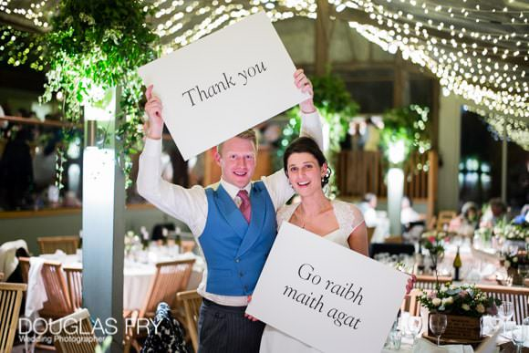 Couple at reception with thank you sign