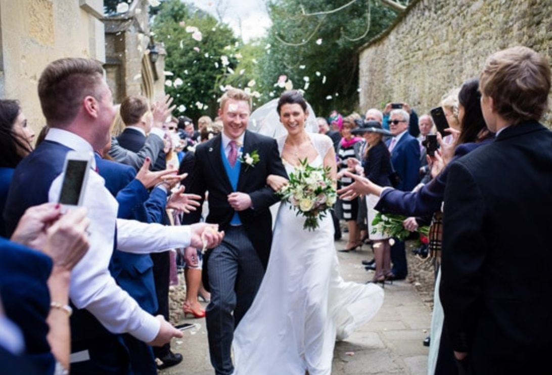 Bride and groom leaving church in Woodstock, Oxfordshire through confetti
