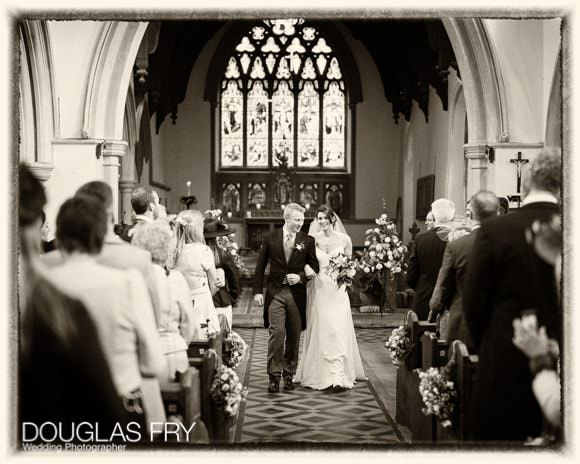 Bride and groom walking down the aisle in Woodstock Church after wedding ceremony