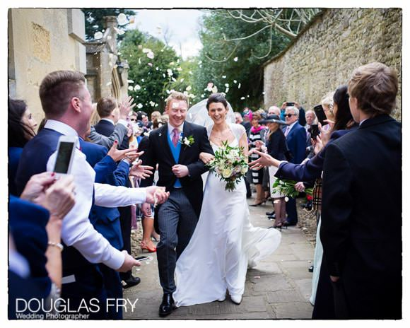 Bride and groom outside church with guests throwing confetti.