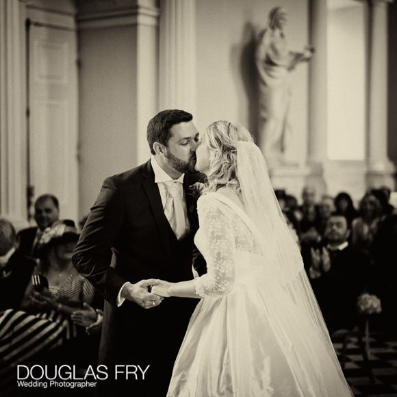 Sepia photograph of bride and groom kissing during Syon ceremony