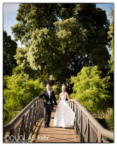 Bride and groom photographed on bridge in the gardens of Syon Park