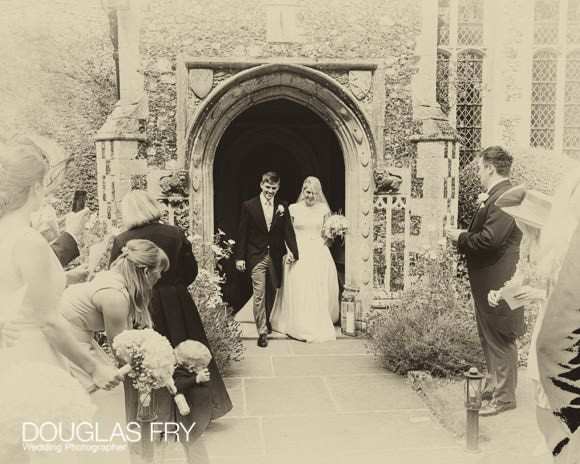 Black and White Photograph of Couple leaving church in Suffolk