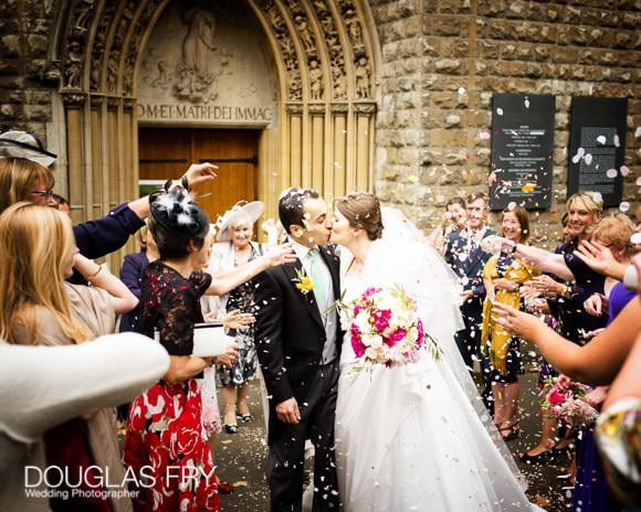 Confetti wedding photograph in front of Farm Street Church in London