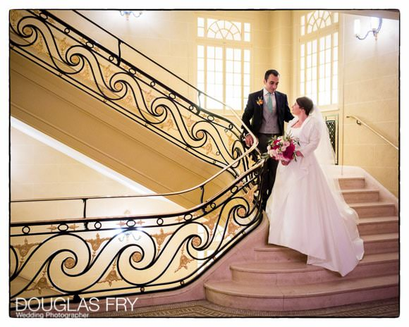 Bride and groom on stairs at Hotel Cafe Royal in London