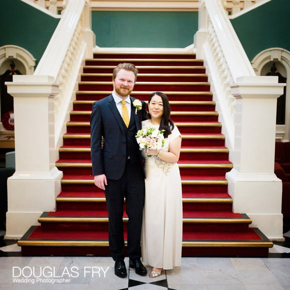Couple on stairs in Woolwich being photographed after wedding ceremony