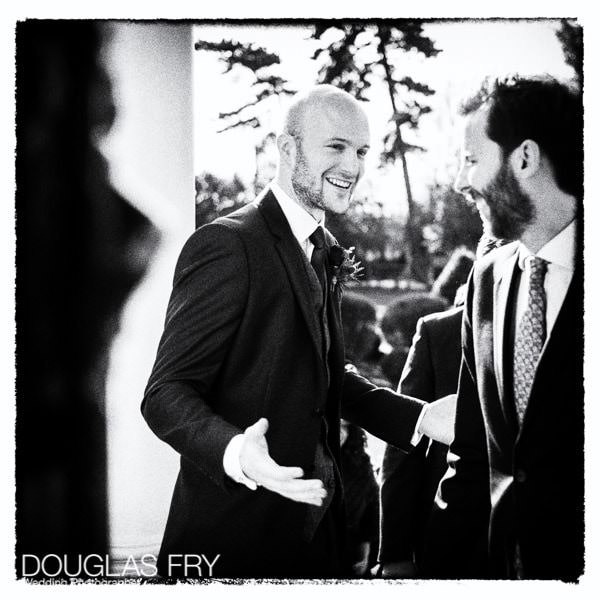 Groom welcoming guests at Hampton Court taken on Leica camera - black and white