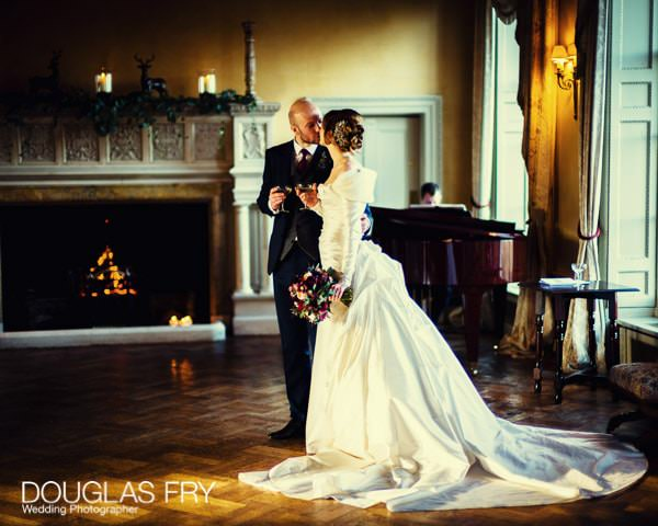 Bride and groom in front of fire at Hampton Court House - Leica picture