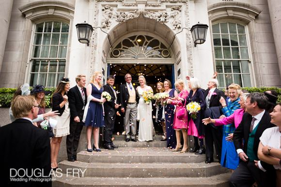 Couple and guests on steps at Chelsea Register office on the Kings Road