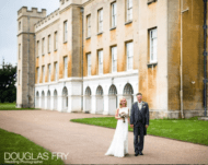 Exterior of Syon Park with bride and groom walking arm in arm during wedding