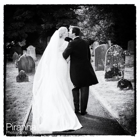 Black and white photograph of bride and groom in graveyard of Crudwell church
