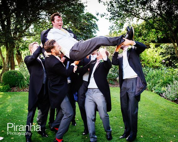 Ushers and groom photographed holding groom aloft