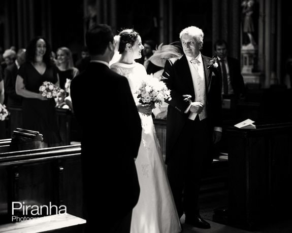 Wedding service at Farm Street Church with bride, groom and father of the bride in black and white