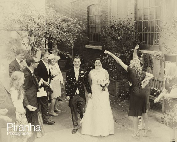 Bride and Groom walking outside chruch with confetti in London - sepia image