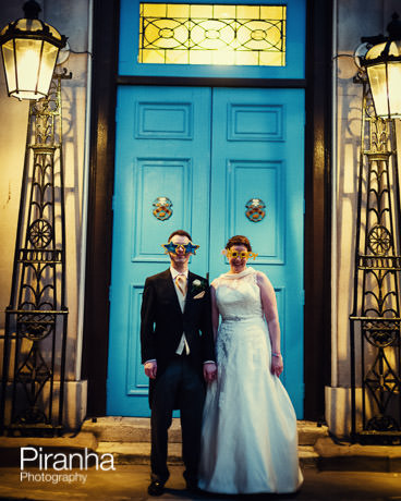 Bride and groom in comedy specatales in front of Stationers' Hall in London during wedding reception