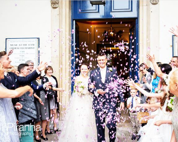 Bride and groom leaving church with confetti in London