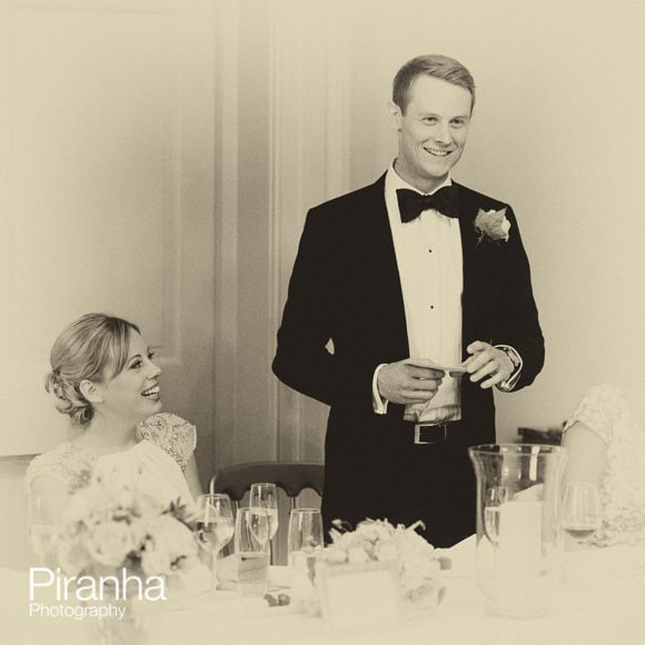 Black and white photograph of groom making speech during wedding breakfast in Greenwich