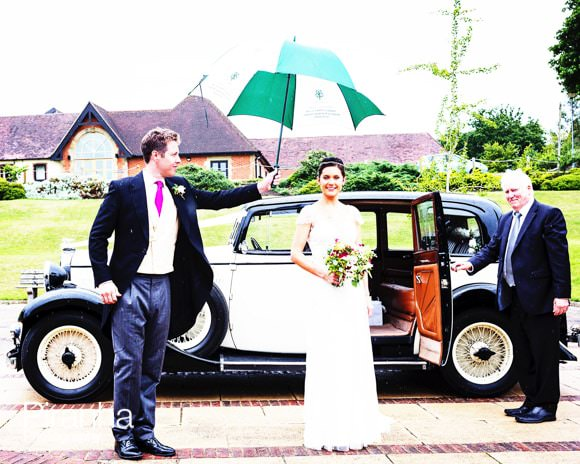 Bride getting out of car with umbrella in rain
