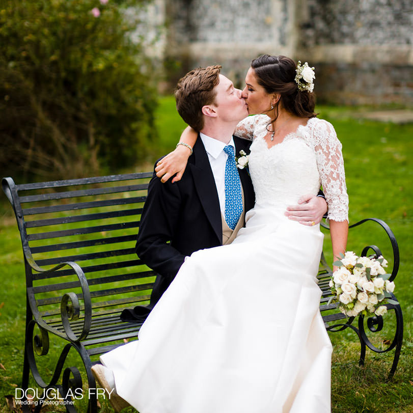 couple kissing sitting on bench outside church after wedding in Hampshire